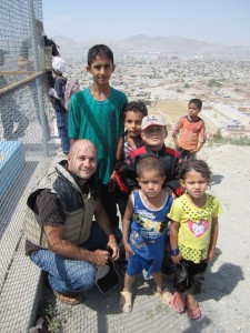 """A small group from the Embassy were visiting various sites around Kabul and stopped to talk to the kids from the local neighbourhood who were playing there. We are wearing bullet-proof vests which we often needed to wear outside the protected embassy or government compounds. on a promiment hill in Kabul where the old national swimming pool is (which was drained of water and used as an execution site during the years of Taliban rule)."